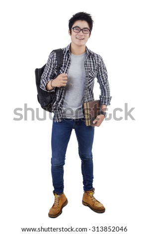 Full length of a clever male high school student standing in the studio while carrying backpack, isolated on white background - stock photo