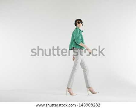 Full length of a cool young woman walking in high heels against white background - stock photo
