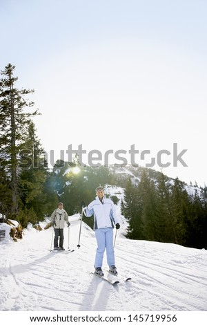 Full length of a couple skiing down slope against trees and sky - stock photo
