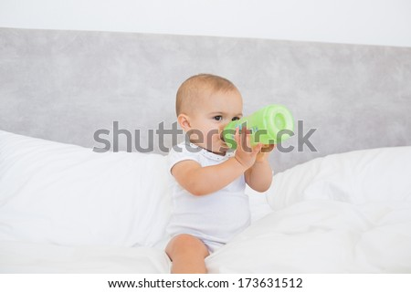 Full length of a cute baby with milk bottle sitting on bed at home