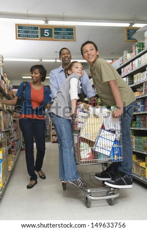 Full length of a family of four shopping in supermarket - stock photo