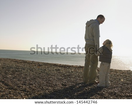 Full length of a father and son looking at each other on beach - stock photo