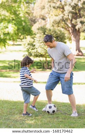 Full length of a father and son playing football in the park - stock photo
