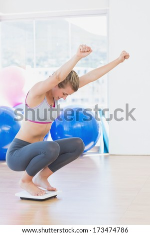Full length of a fit young woman cheering on scale in a bright exercise room - stock photo