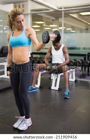 Full length of a fit young woman exercising with dumbbell in the gym