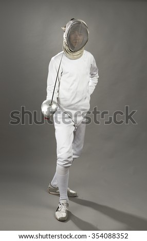 Full length of a foil fencer on gray background.  - stock photo