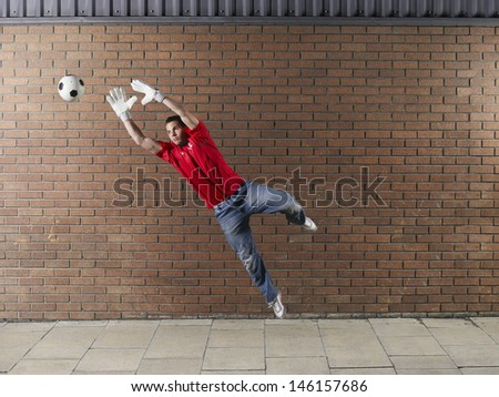 Full length of a goalkeeper reaching for football against brick wall - stock photo