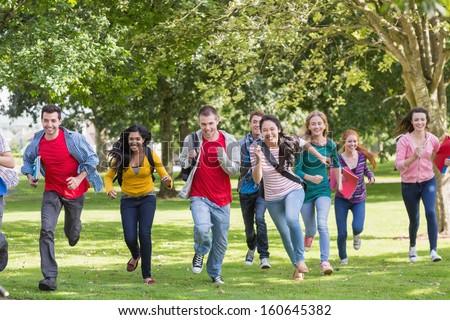 Full length of a group of college students running in the park - stock photo