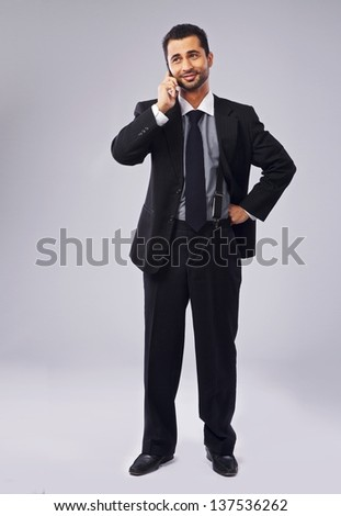 Full length of a handsome young executive talking on the phone - stock photo