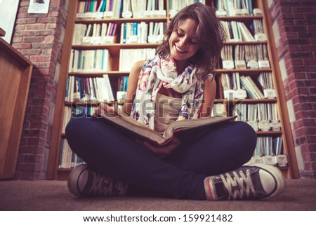 Full length of a happy female student sitting against bookshelf and reading a book on the library floor - stock photo