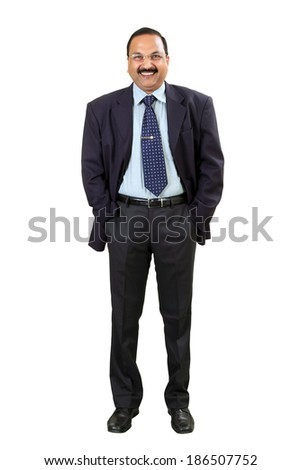 Full length of a happy Indian business man standing with hands in pocket isolated over white background. Studio shot. - stock photo