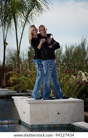 Full length of a happy playful couple posing next to a pool. A green winter desert landscape is in the background. - stock photo