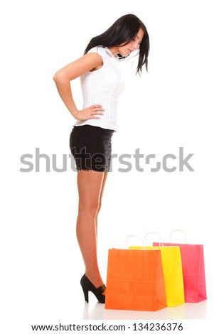 Full length of a happy young lady holding shopping bags against isolated white background