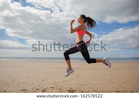 Full length of a healthy young woman jogging on shore at beach - stock photo