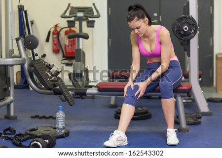 Full length of a healthy young woman with an injured knee sitting in the gym - stock photo