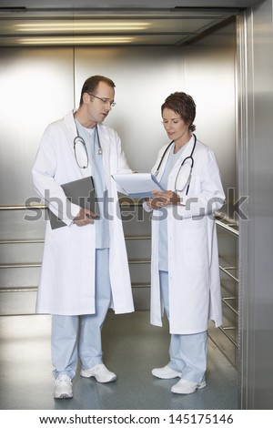 Full length of a male and female physicians discussing chart in hospital elevator - stock photo