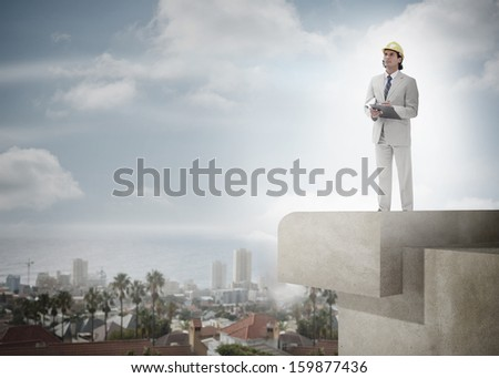 Full length of a male architect with hard hat and clipboard against the sky and cityscape - stock photo