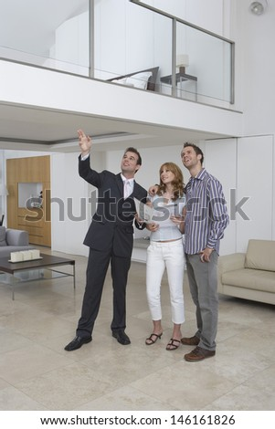 Full length of a male real estate agent showing couple new home - stock photo