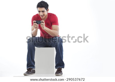 Full length of a man using phone for text messaging against white background - stock photo