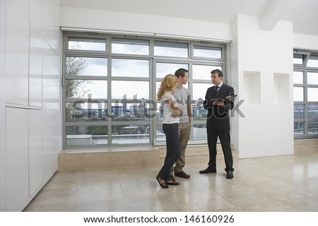 Full length of a real estate agent showing couple new apartment - stock photo