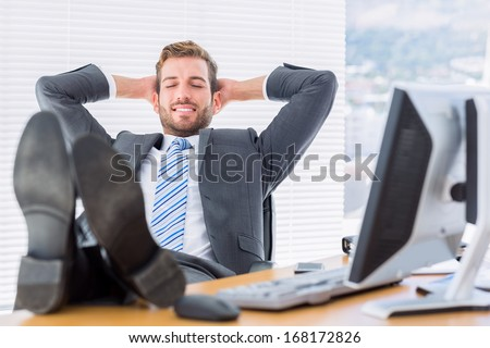 Full length of a relaxed young businessman sitting with legs on desk at office