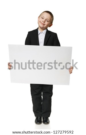 Full length of a schoolboy in black suit holding blank placard / banner, over white background - stock photo