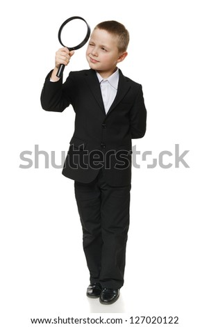 Full length of a schoolboy in black suit looking through the magnifying glass, over white background - stock photo