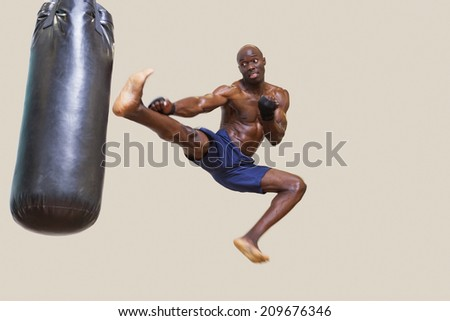 Full length of a shirtless muscular boxer kicking punching bag over white background - stock photo