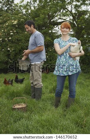 Full length of a smiling couple feeding hens on grassland