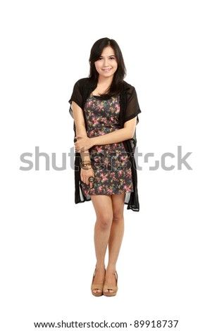 Full length of a smiling young female model standing over white background - stock photo