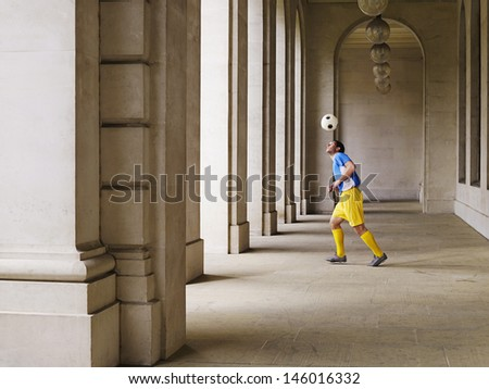 Full length of a soccer player bouncing ball Off head in portico - stock photo