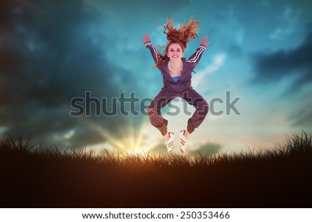 Full length of a sporty young blond jumping against blue sky over grass - stock photo