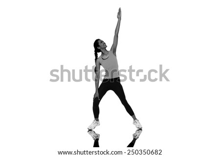 Full length of a sporty young woman stretching hand against mirror - stock photo