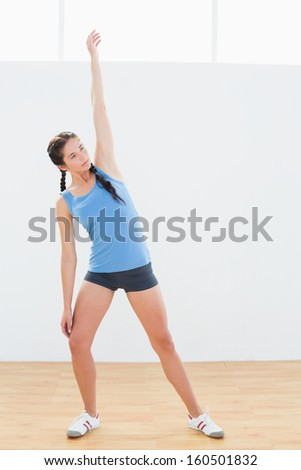 Full length of a sporty young woman stretching hand in fitness center
