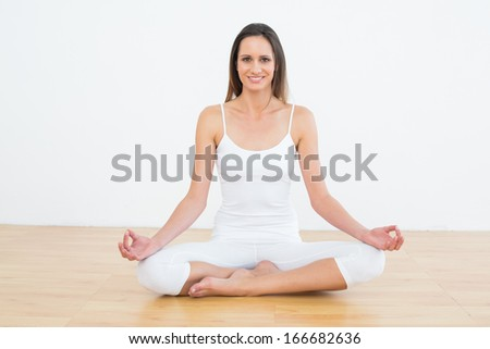 Full length of a toned young woman in lotus pose at a fitness studio - stock photo