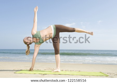 Full length of a woman in sportswear doing yoga (Half Moon pose) on mat at beach - stock photo