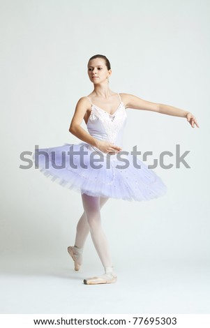 Full length of a young and beautiful ballet dancer practicing against white background