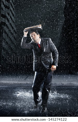 Full length of a young businessman covering head with binder while running through rain - stock photo