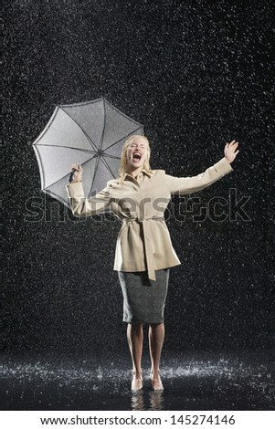 Full length of a young businesswoman in overcoat with umbrella singing in the rain - stock photo