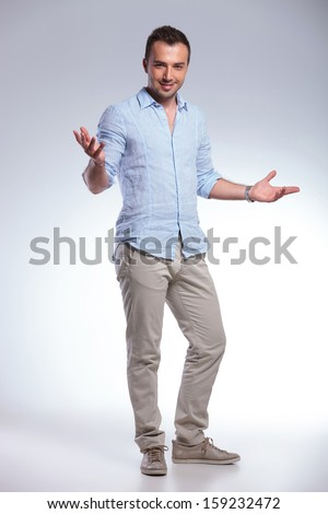 full length of a young casual man welcoming you with his arms wide open and a smile. on gray background - stock photo