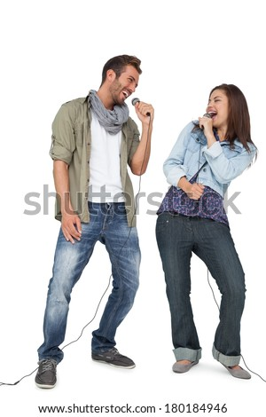 Full length of a young couple singing into microphones over white background - stock photo