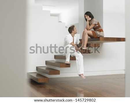 Full length of a young couple sitting on stairs in house - stock photo