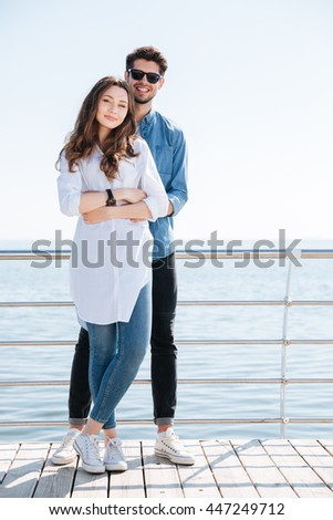 Full length of a young happy couple standing together and hugging at the seaside - stock photo