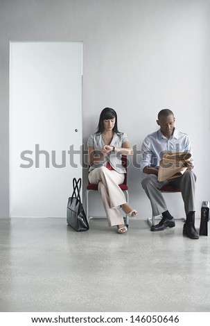 Full length of a young man and woman sitting on chairs in office corridor - stock photo