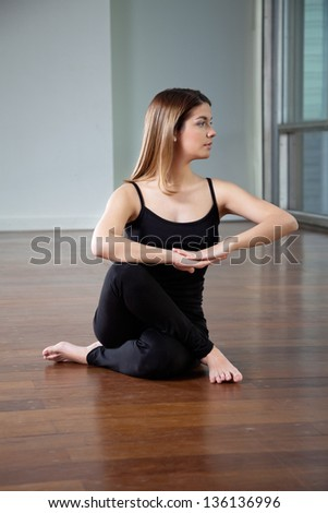 Full length of a young woman practicing yoga exercise on wooden floor - stock photo