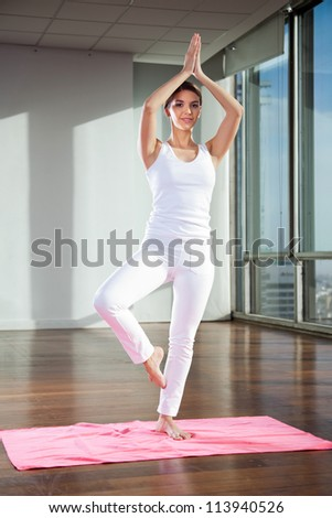 Full length of a young woman practicing yoga in Tree position on mat - stock photo