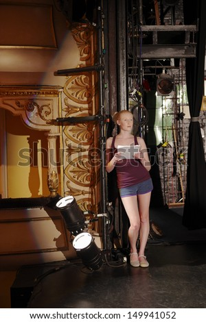 Full length of a young woman reading script backstage - stock photo