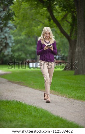Full length of a young woman using smart phone as she walks in park