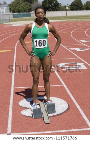 Full length of African American female athlete at starting block on race track - stock photo