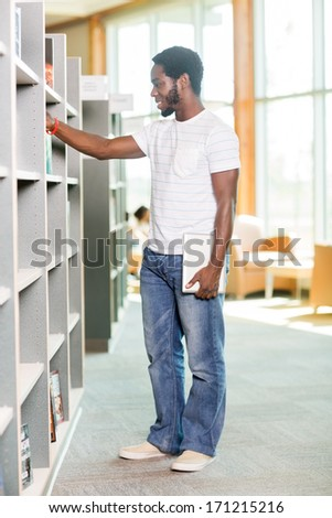 Full length of African American student with digital tablet choosing book in bookstore - stock photo